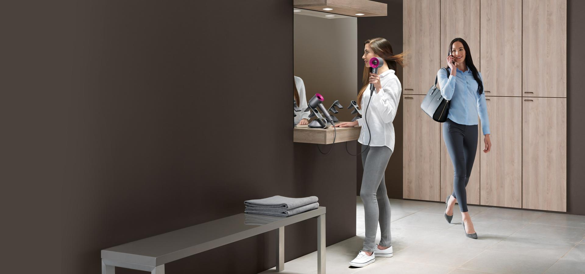 Two women in a changing room. One using Dyson Supersonic.