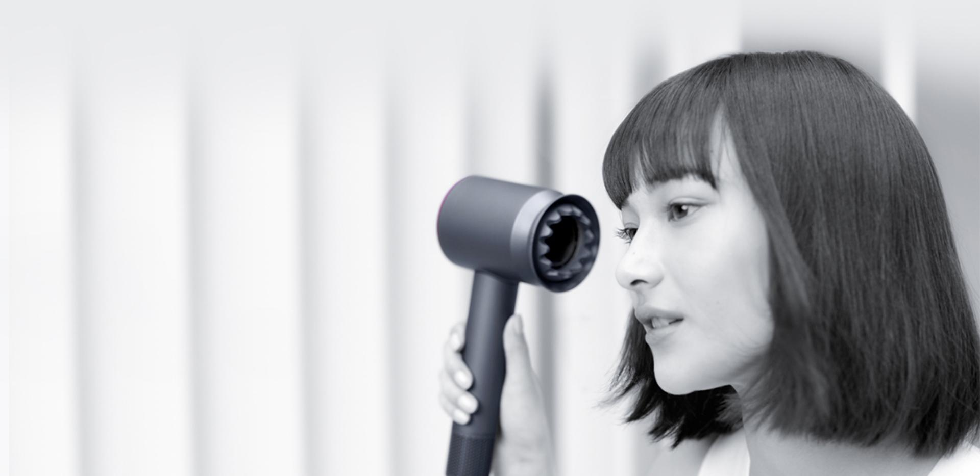 Woman drying her hair with the Dyson Supersonic hair dryer