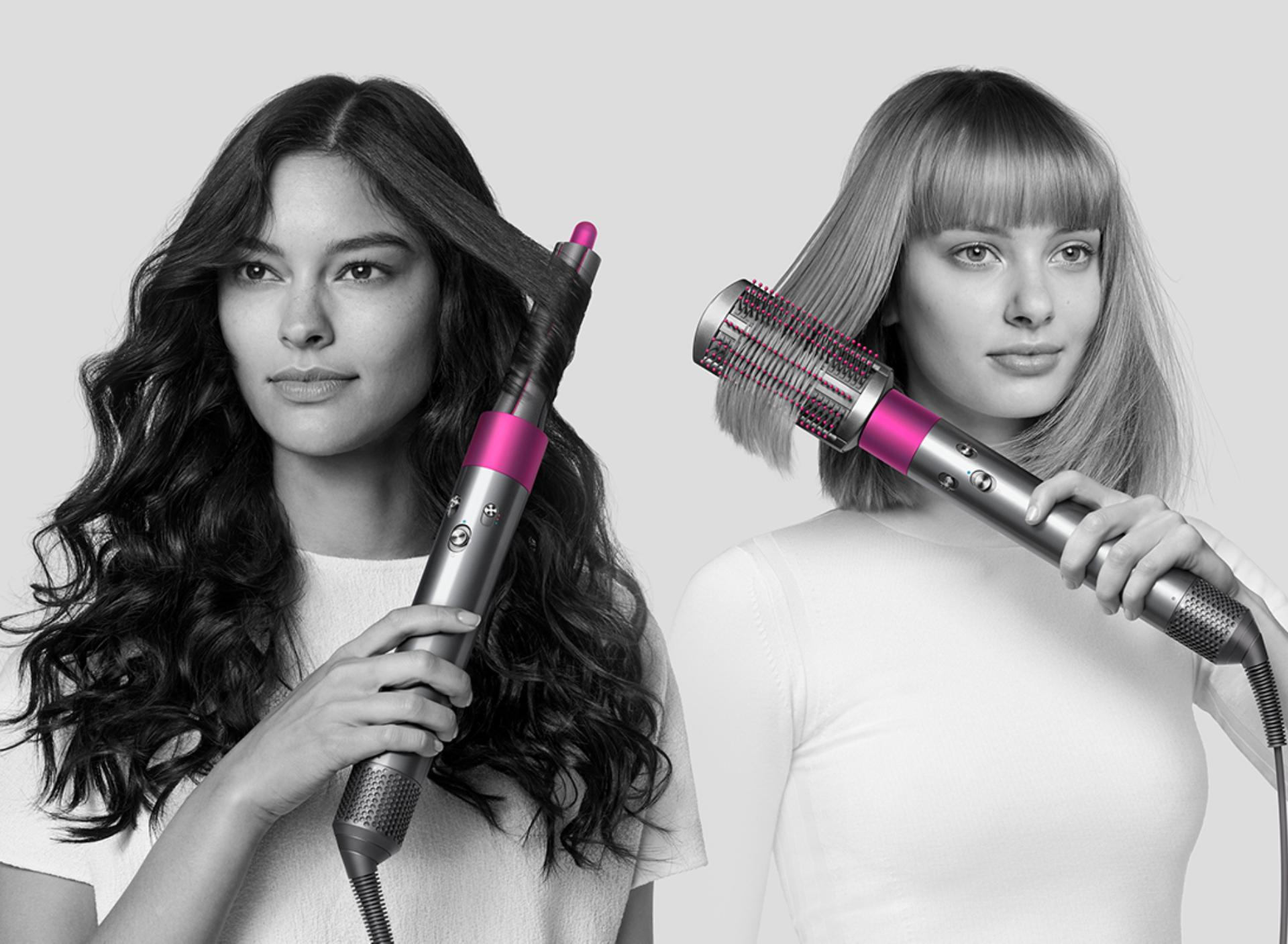 Two models using the Dyson Airwrap styler to curl hair