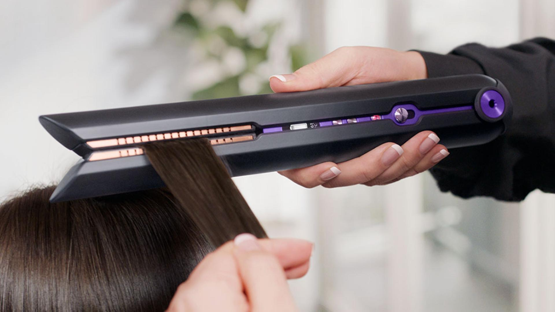 Professional stylist using the Dyson Corrale hair straightener