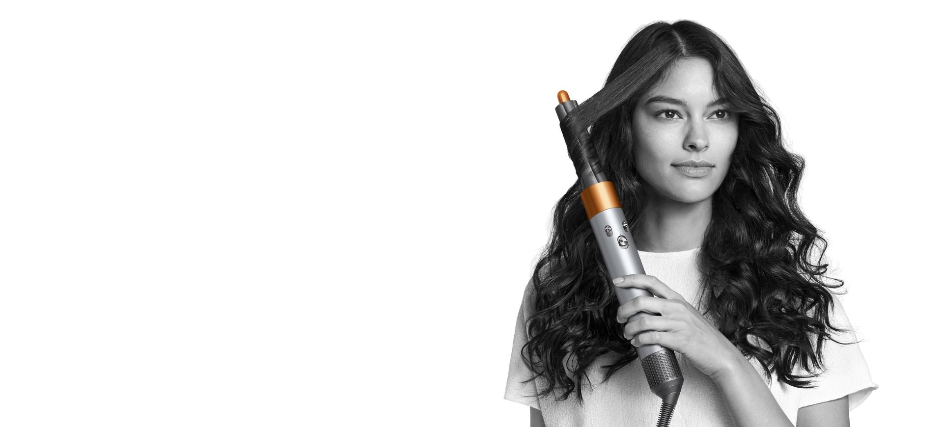 Woman styles hair with copper Dyson Airwrap styler