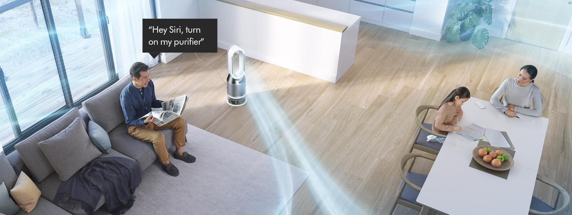 Man on a sofa asking Dyson purifier to purify a room.