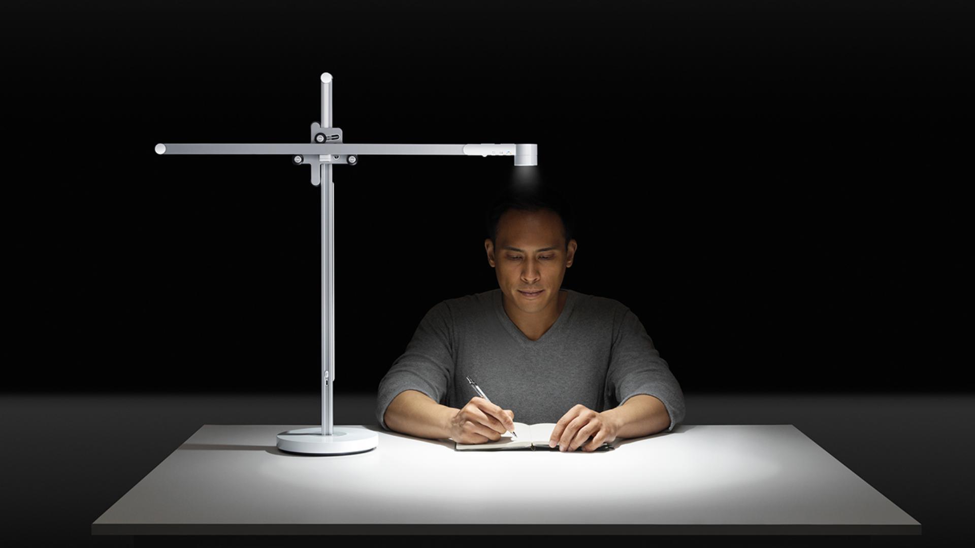 Un hombre trabajando bajo una potente luz de escritorio