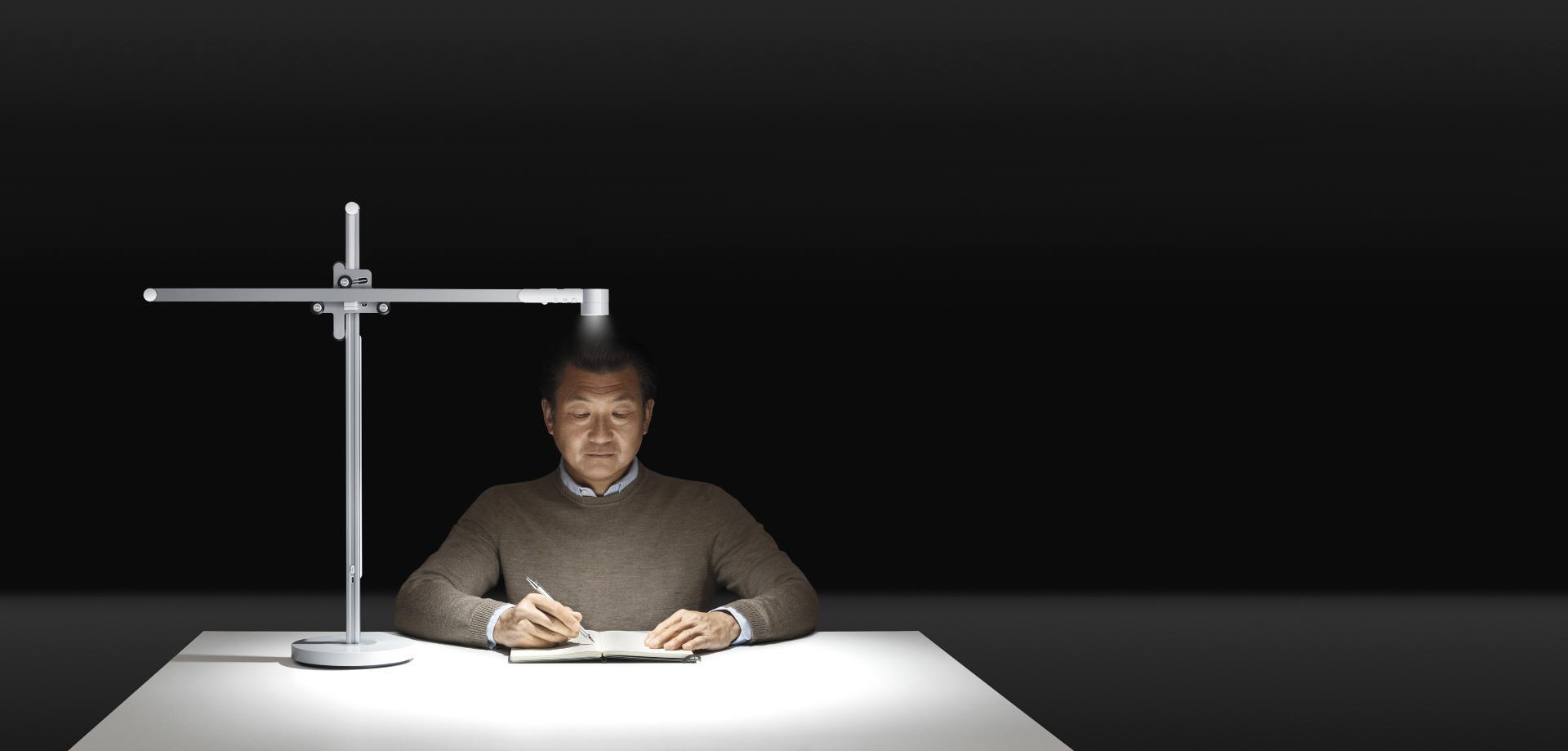 Un hombre maduro lee bajo una potente luz