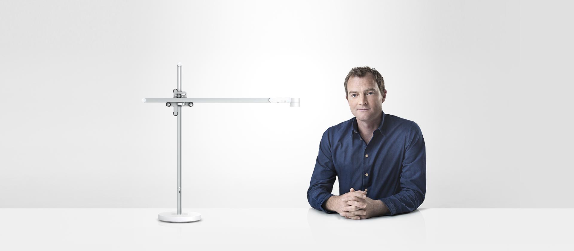 Jake Dyson sentado junto a la lámpara de trabajo Dyson Lightcycle