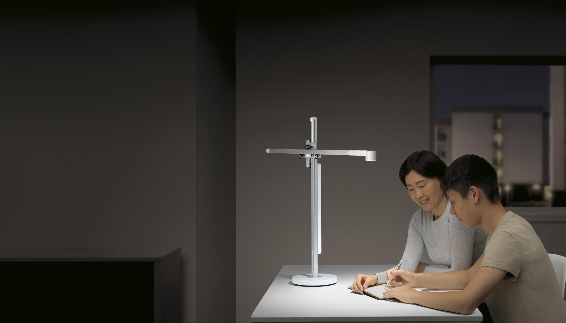 Un adolescente estudia con su mamá con una potente lámpara de escritorio