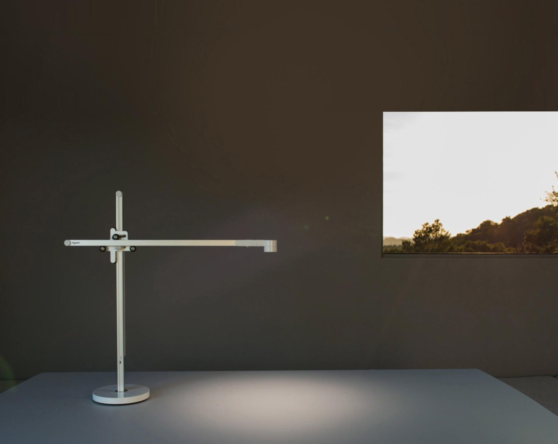 La lámpara de trabajo Dyson Lightcycle se ajusta con la luz solar afuera de una ventana