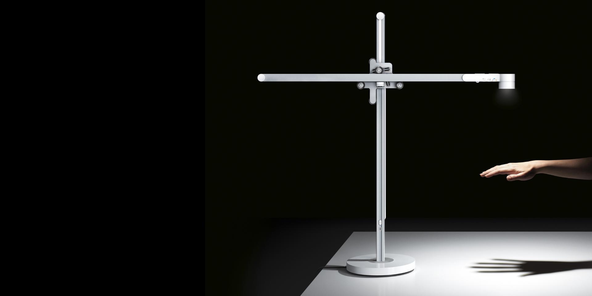 La lámpara de trabajo Dyson Lightcycle brillando con potencia en una mano