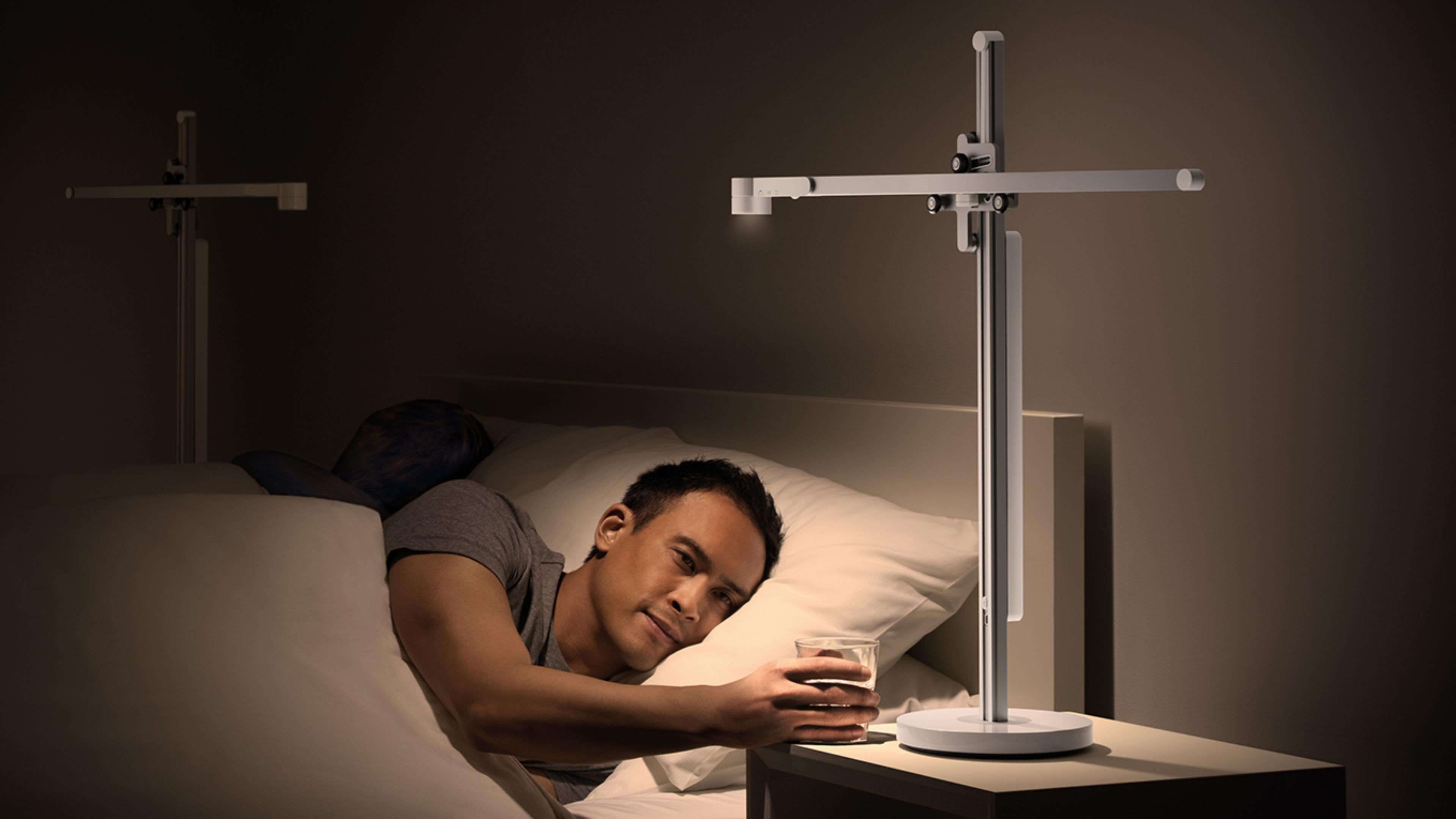 Hombre usando la lámpara Dyson Lightcycle antes de dormir
