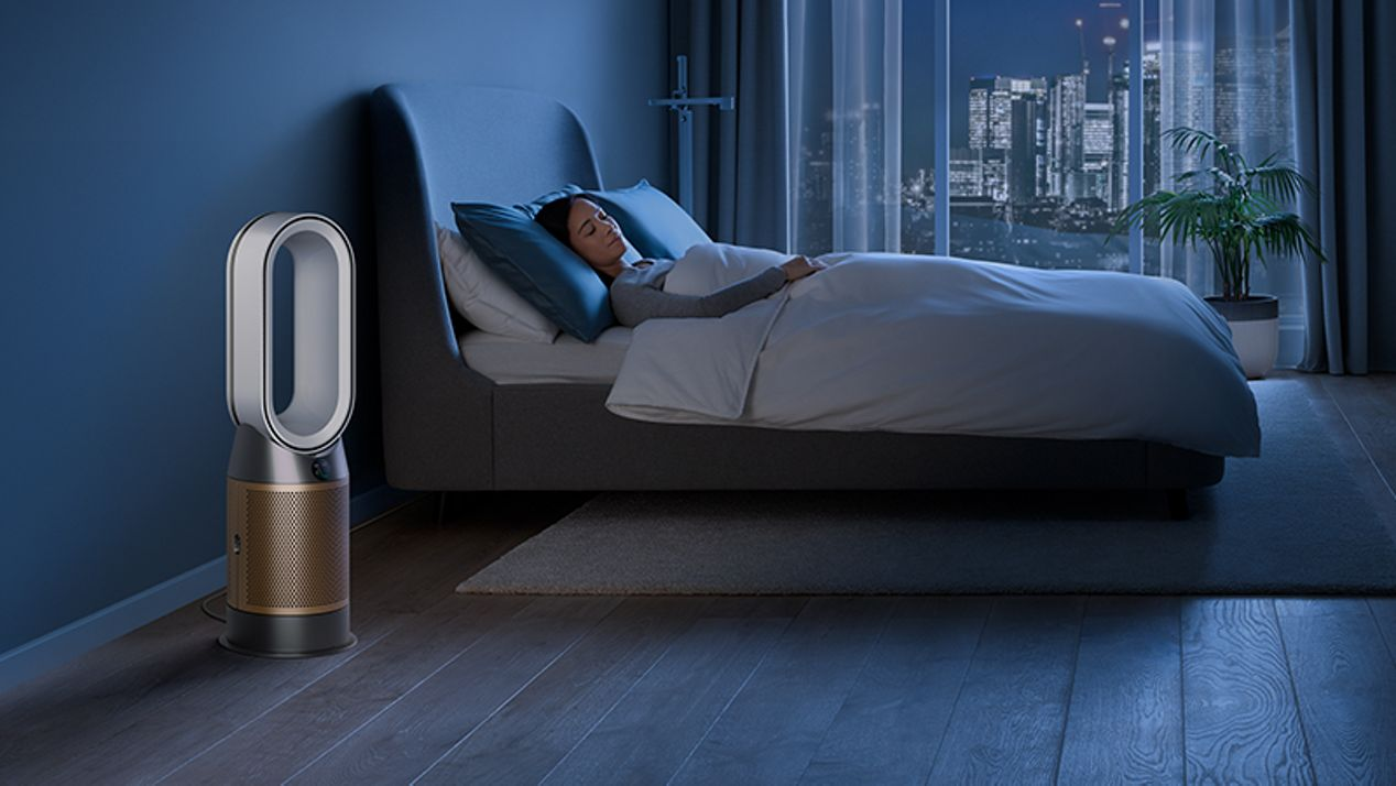 Dyson air purifier in a dark bedroom with someone sleeping peacefully