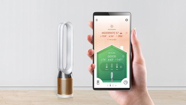 Рука, держащая смартфон перед очистителем Dyson. На экране телефона отображается приложение Dyson Link.