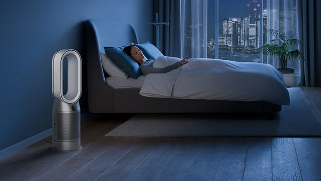 Dyson purifier in a dark bedroom with someone sleeping peacefully