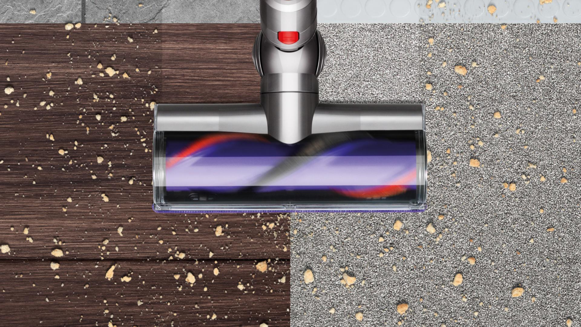 The Dyson Cyclone V10 vacuum cleaner's torque drive cleaner head picking up debris across multiple floor surfaces.