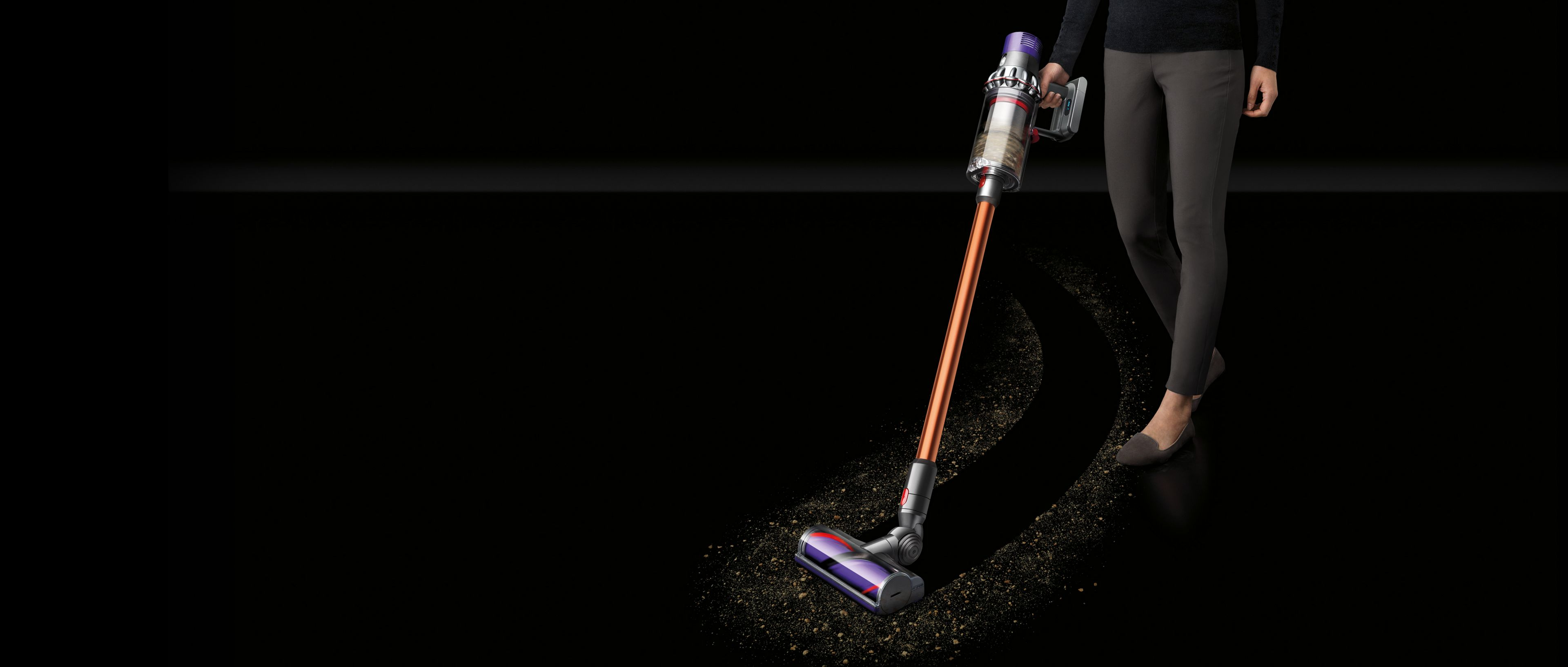 Woman cleaning dirt with Dyson Cyclone V10™ vacuum