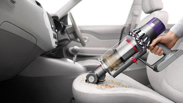 Le DysonCycloneV10 utilisé en tant qu'aspirateur à main pour le nettoyage de l'habitacle d'une voiture