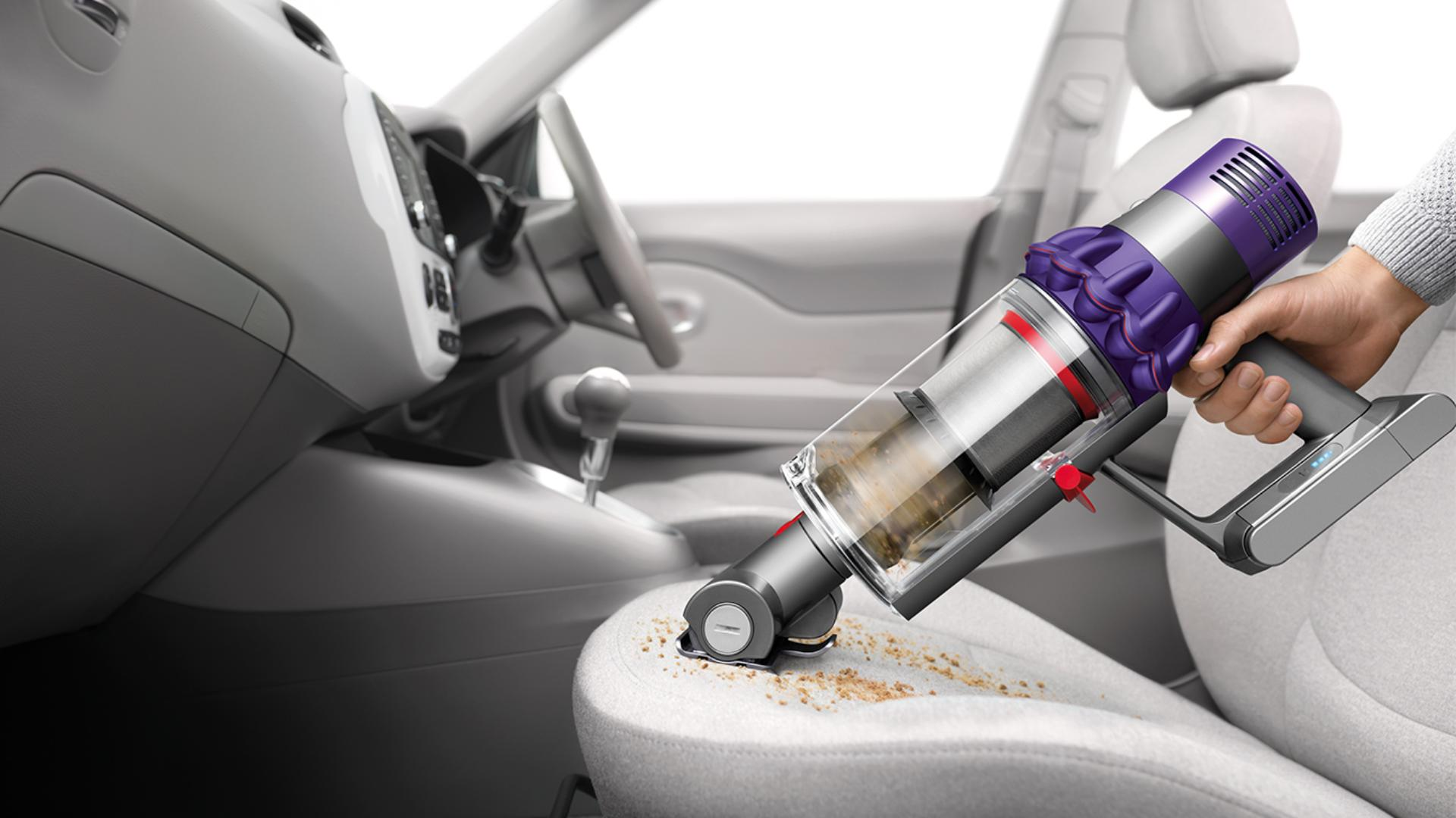 Dyson Cyclone V10 vacuum cleaner being used a handheld to clean car interior