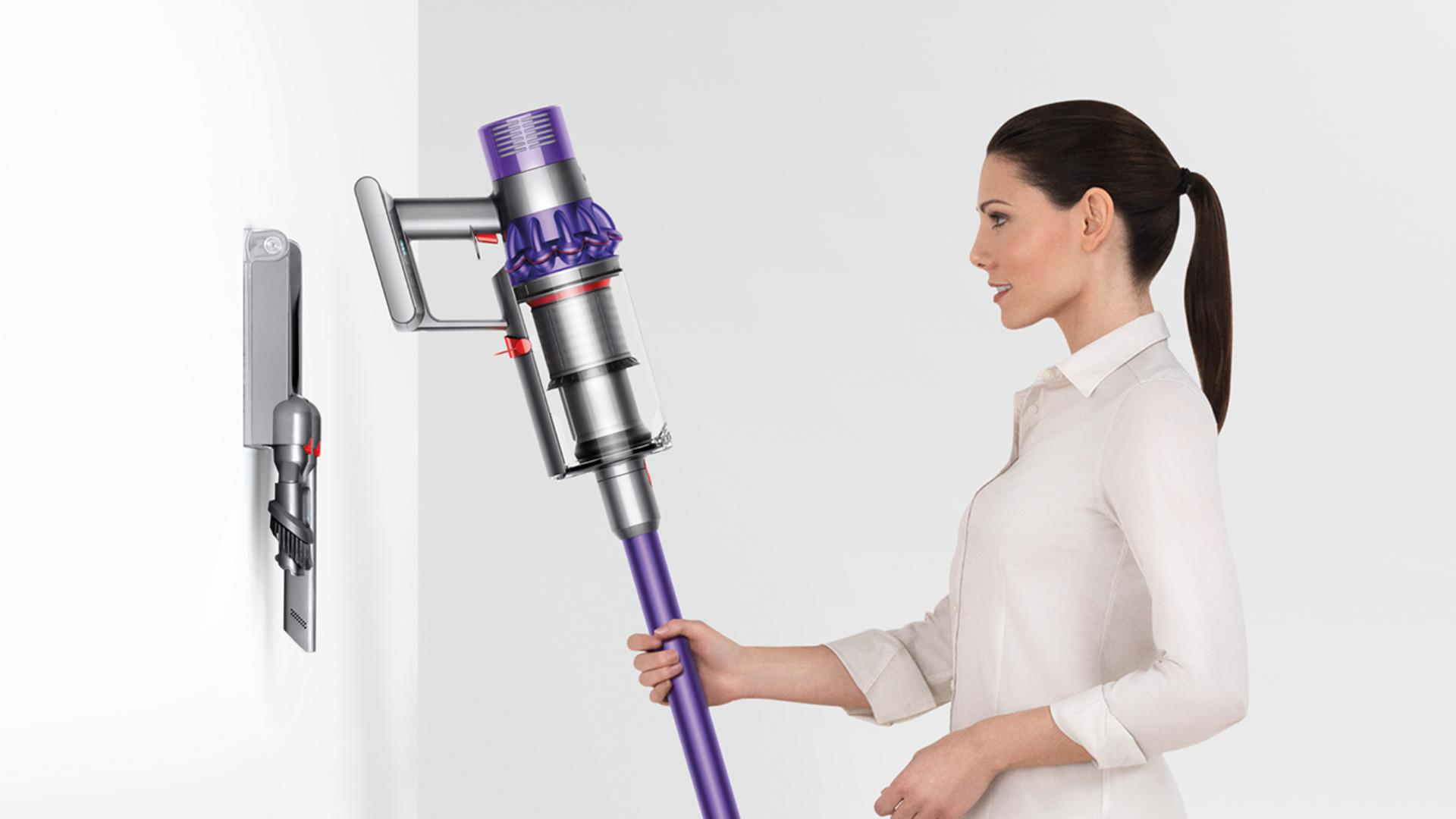 Woman droping Dyson Cyclone V10 neatly inot docking station