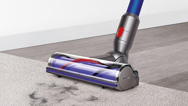 La brosse à entraînement direct du DysonV7 nettoyant une moquette et un sol dur