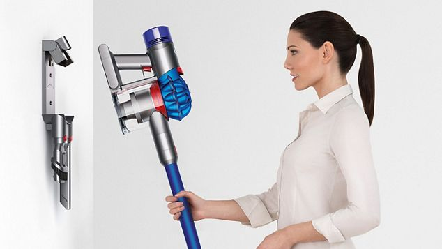 Woman placing Dyson V7 vacuum back into storage dock