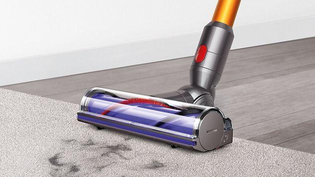 La brosse à entraînement direct du DysonV8 nettoyant une moquette et un sol dur