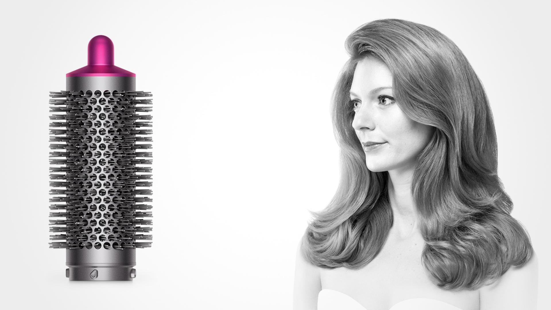 Photograph of a woman and a round volumising brush (Nickel/Fuschia).