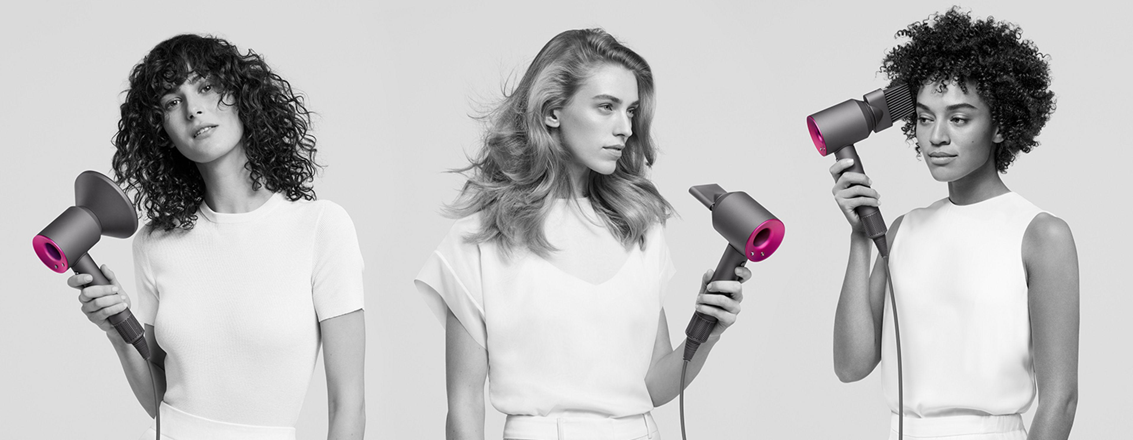 Trois femmes en train d'utiliser le sèche-cheveux Dyson Supersonic