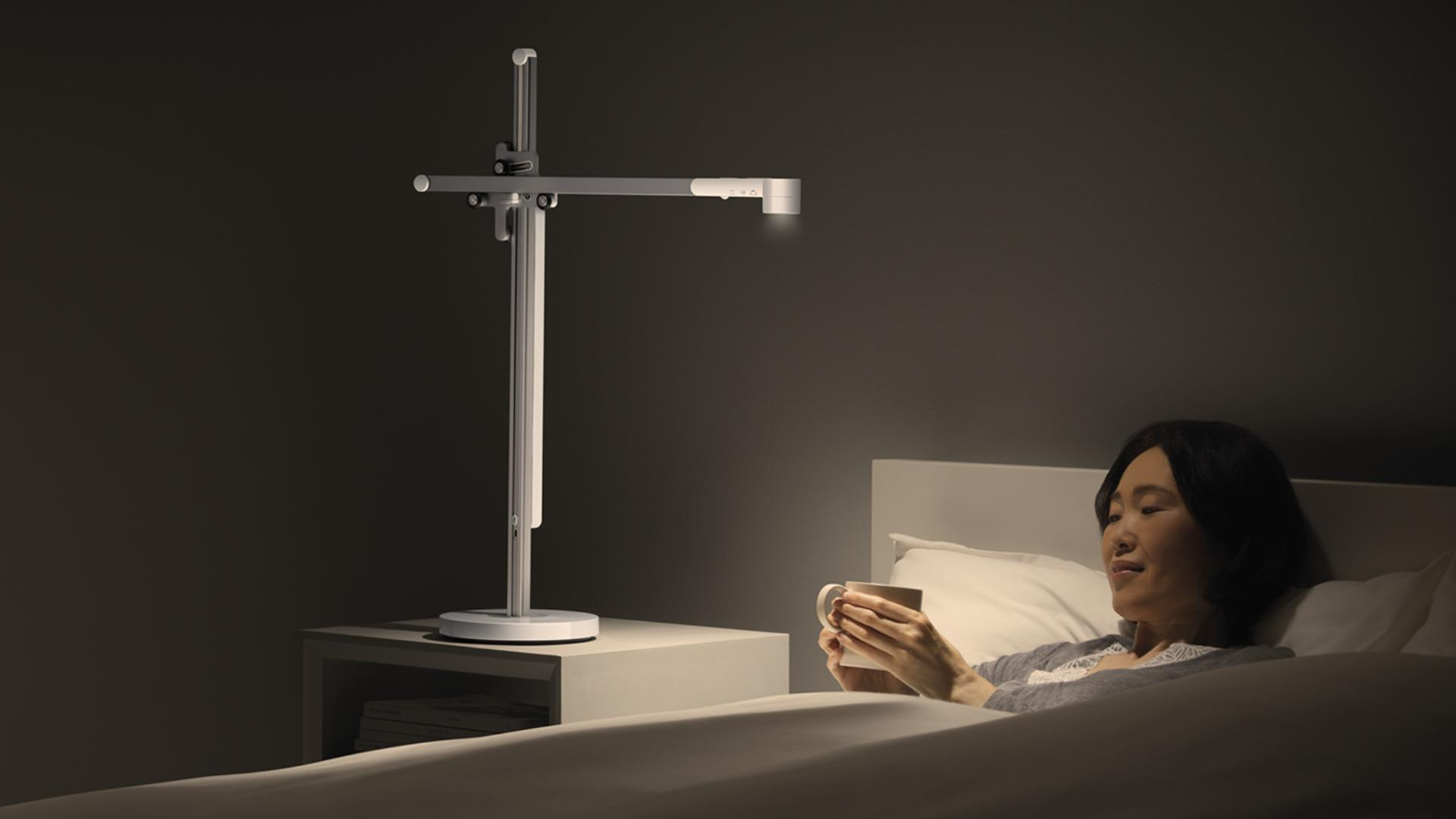 Woman reading in bed beside Dyson task light