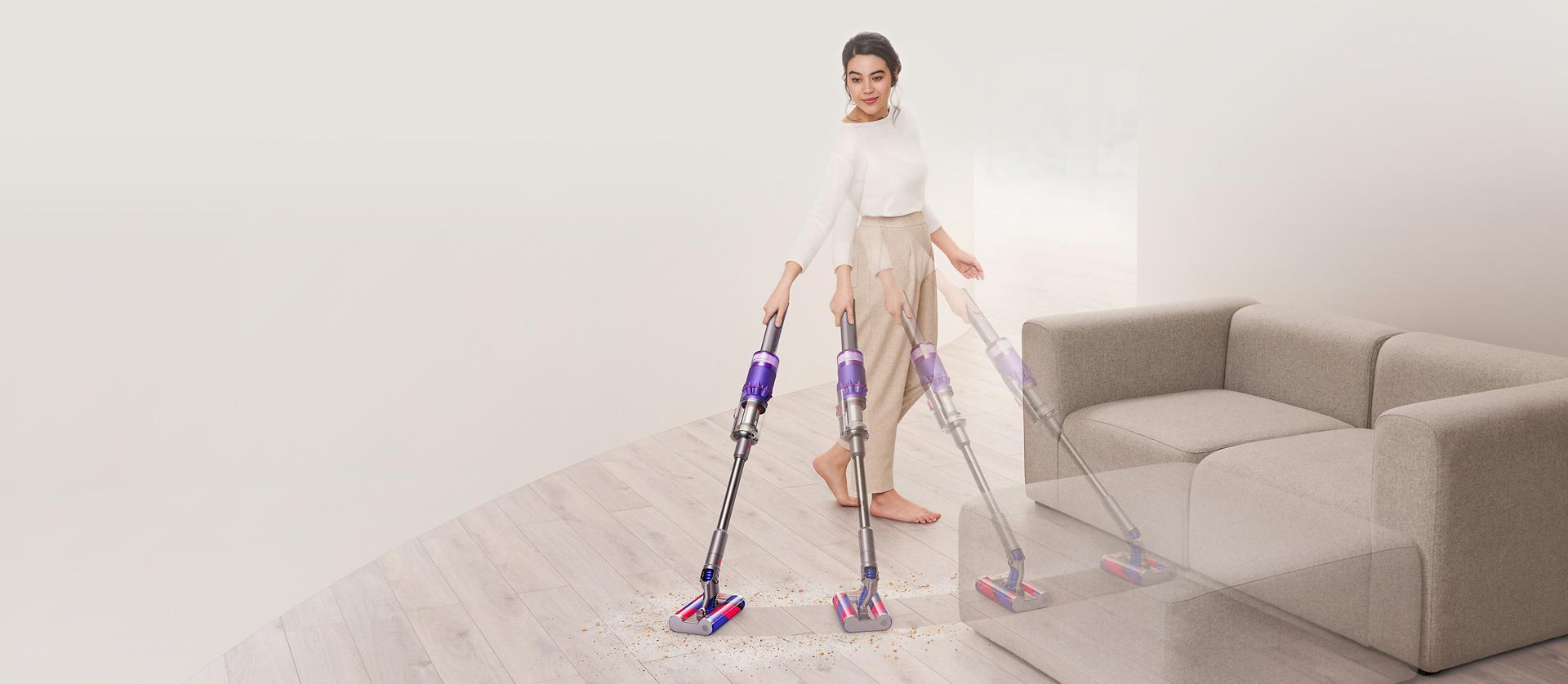 Mujer aspirando piso duro alrededor de un sofá con la aspiradora Dyson Omni-glide™.
