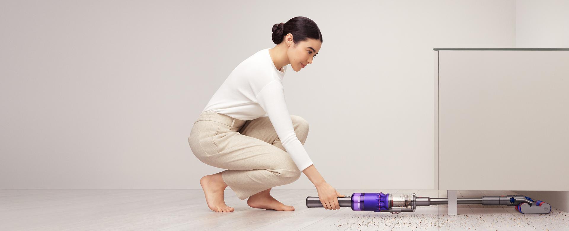 Mujer usando la aspiradora Dyson Omni-glide™ para limpiar debajo de una alacena.